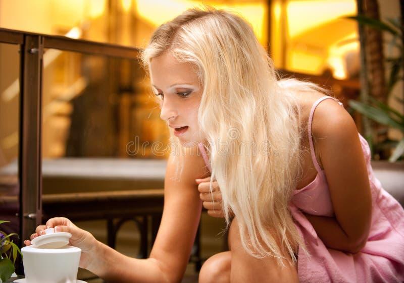 La muchacha abre el tazón de fuente de azúcar fotografía de archivo
