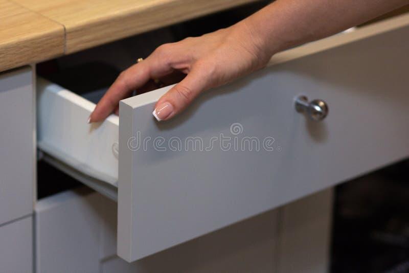 La muchacha abrió una caja blanca de la cocina foto de archivo libre de regalías