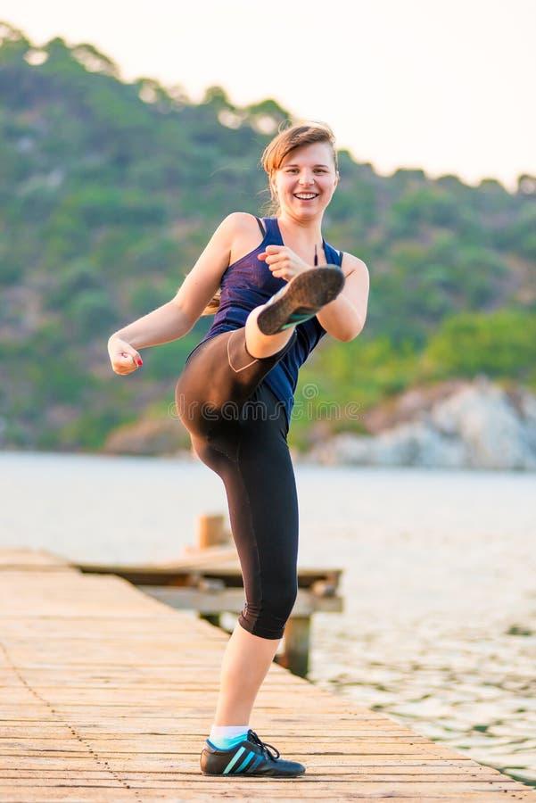 La muchacha activa entra para los deportes cerca del mar imagen de archivo