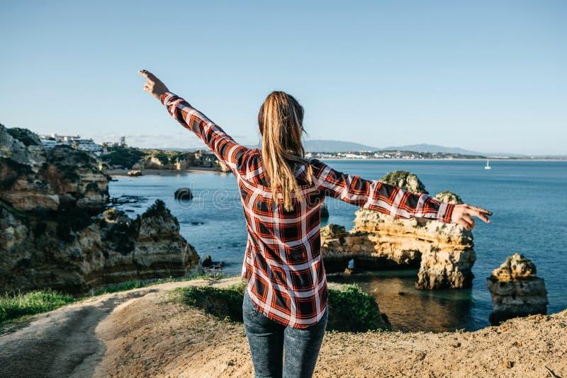 La muchacha admira una hermosa vista del Océano Atlántico imagenes de archivo