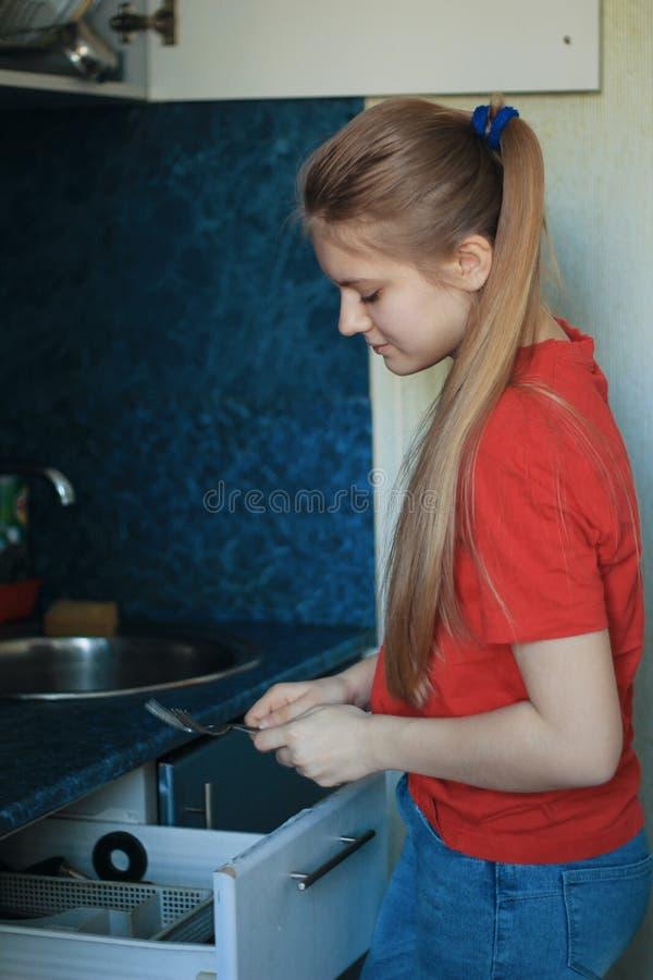 La muchacha adolescente 14 años de viejo está lavando platos en la cocina fotos de archivo libres de regalías