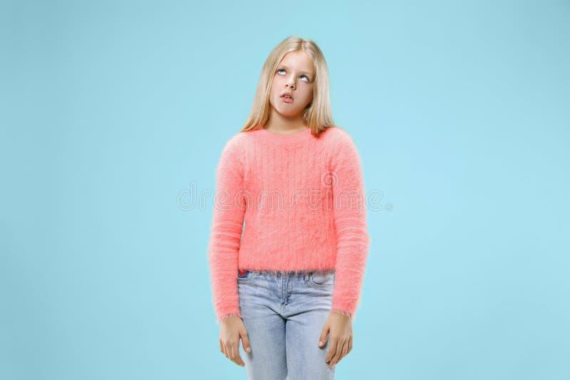 La muchacha adolescente aburrida hermosa agujereó en fondo azul fotos de archivo