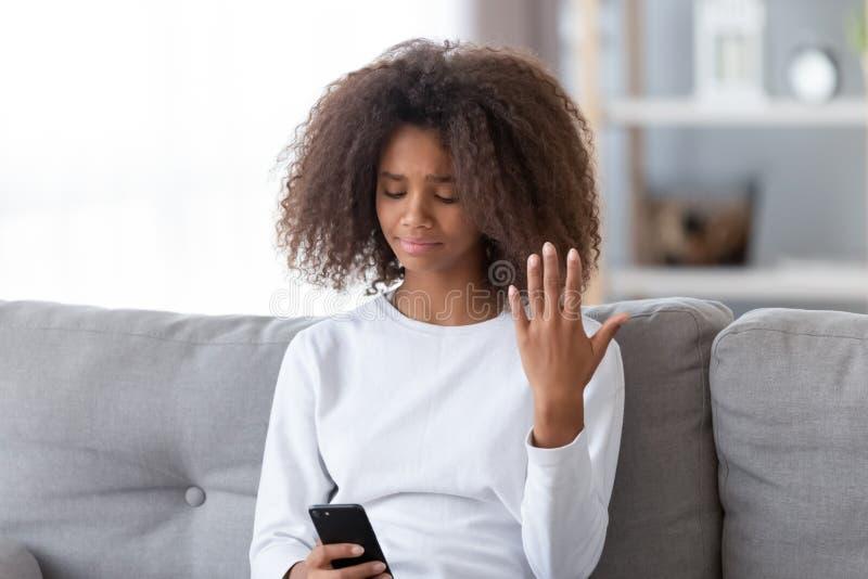 La muchacha adolescente afroamericana trastornada usando el teléfono, recibió el mensaje desagradable foto de archivo libre de regalías