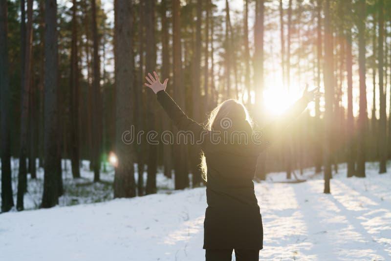 La muchacha adolescente aumentó las manos de detrás en bosque del pino del invierno en puesta del sol fotos de archivo