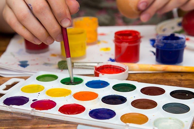 La muchacha adolescente dibuja en una hoja blanca de pinturas coloreadas multi imagenes de archivo