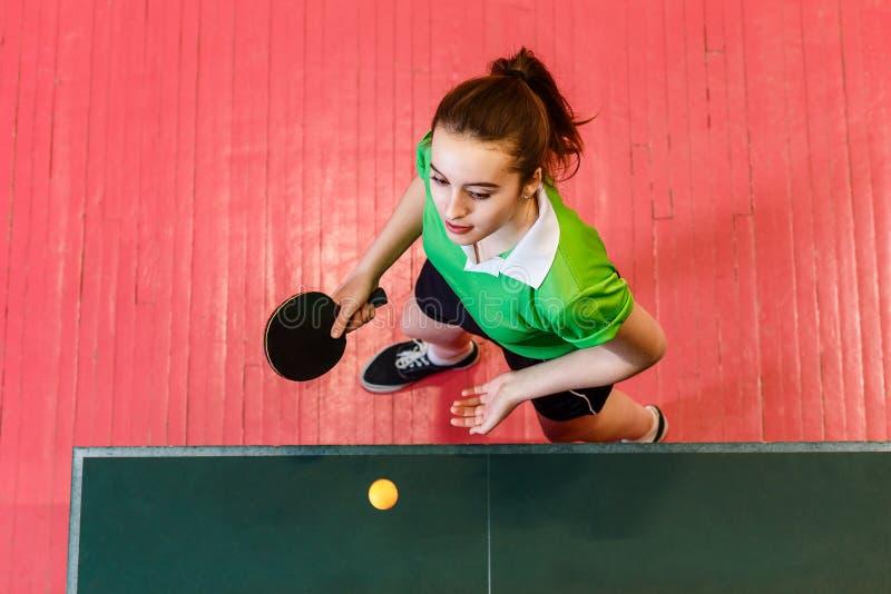la muchacha adolescente Dieciséis-año-vieja hace un servicio de la bola en los tenis de mesa, visión superior Adolescencias y pin foto de archivo libre de regalías