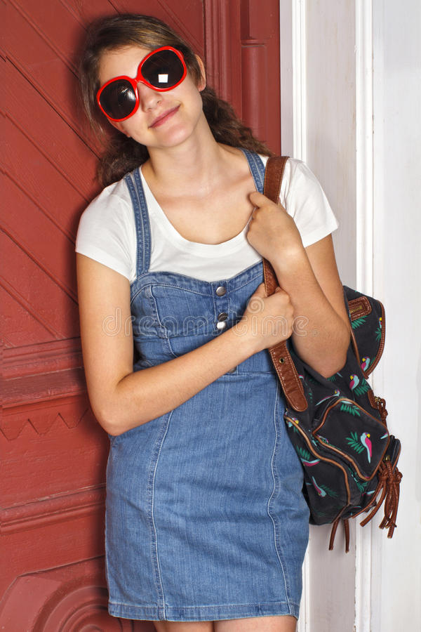 La muchacha adolescente en dril de algodón se inclina contra puerta roja. imagen de archivo libre de regalías