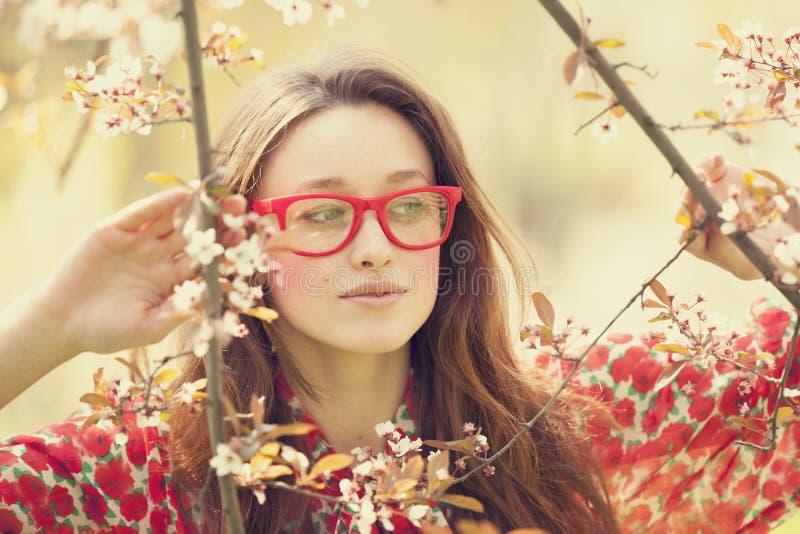 La muchacha adolescente en vidrios acerca al árbol del flor fotografía de archivo libre de regalías