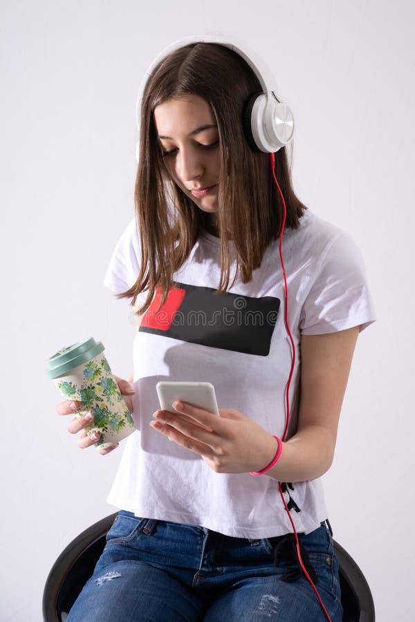 La muchacha adolescente escucha la música en el auricular y escribe el mensaje en el teléfono celular y el café de consumición imagenes de archivo