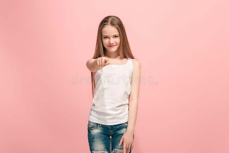 La muchacha adolescente feliz que señala a usted, medio retrato del primer de la longitud en fondo rosado foto de archivo