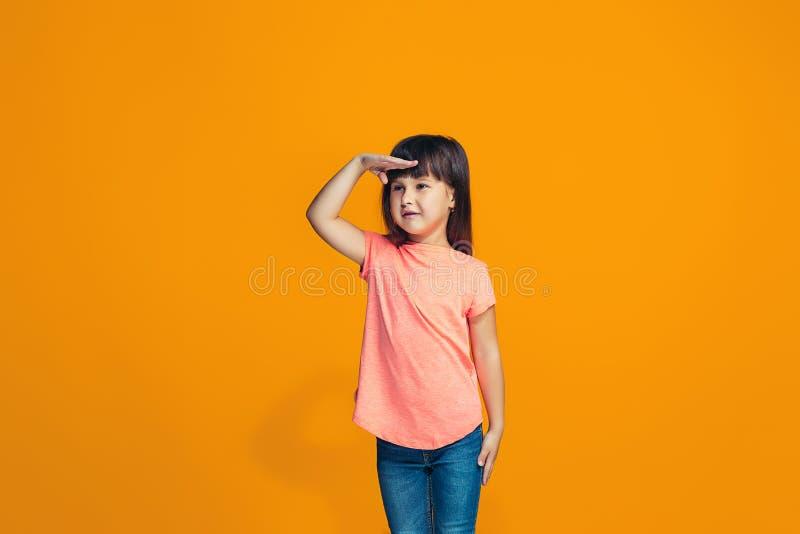 La muchacha adolescente feliz que se opone y que sonríe contra fondo anaranjado imagen de archivo
