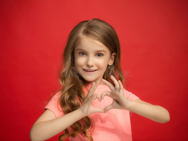 La muchacha adolescente feliz que se opone y que sonríe contra fondo rojo imagen de archivo