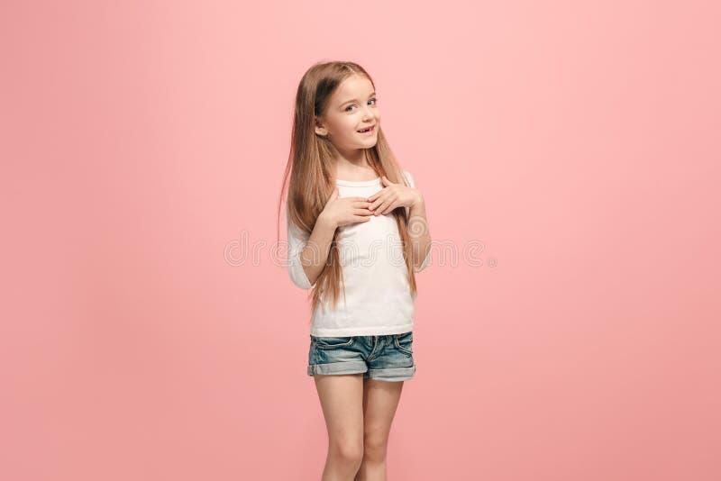 La muchacha adolescente feliz que se opone y que sonríe contra fondo rosado foto de archivo