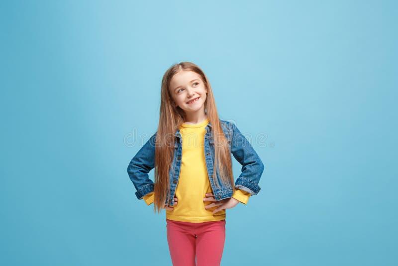 La muchacha adolescente feliz que se opone y que sonríe contra fondo rosado fotografía de archivo