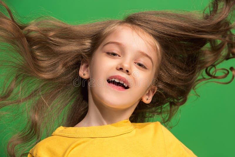 La muchacha adolescente feliz que se opone y que sonríe contra fondo verde imágenes de archivo libres de regalías