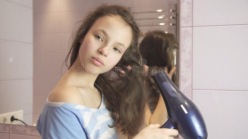 La muchacha adolescente hermosa el cabello seco un hairdryer en cuarto de baño fotografía de archivo