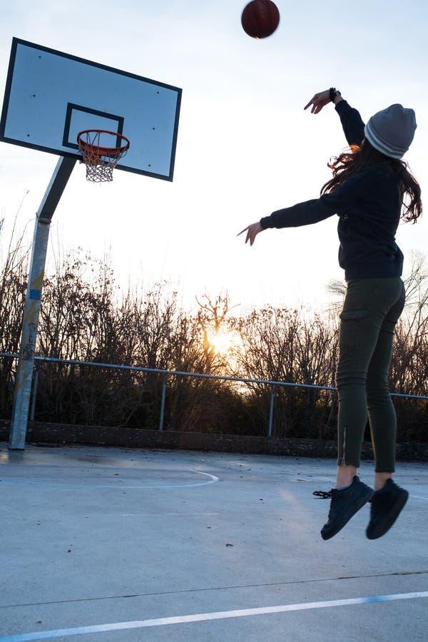 La muchacha adolescente joven está jugando a baloncesto afuera imagenes de archivo