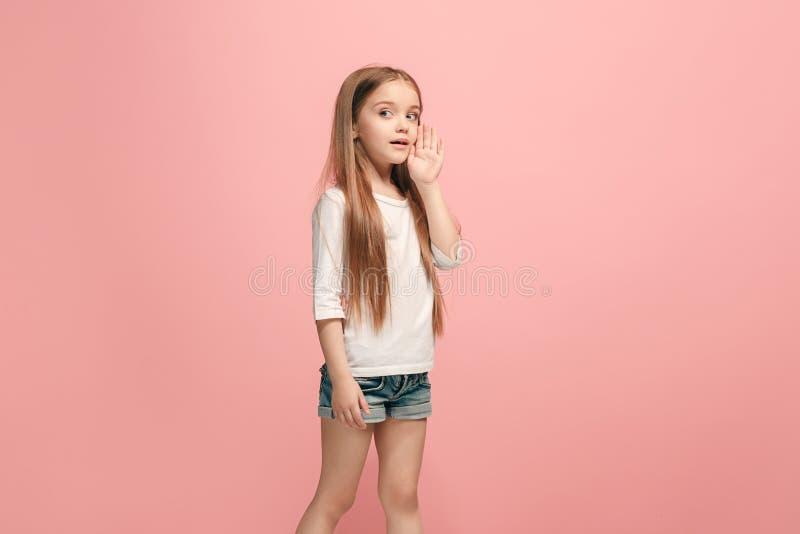 La muchacha adolescente joven que susurra un secreto detrás de ella entrega el fondo rosado foto de archivo libre de regalías