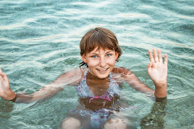 La muchacha adolescente linda joven se baña en el mar con una sonrisa feliz y agita su mano imagen de archivo libre de regalías