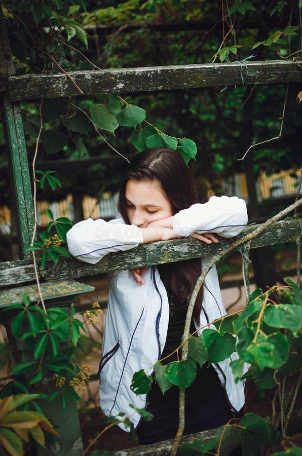 La muchacha adolescente se coloca en la calle contra la perspectiva de las hojas verdes imagenes de archivo
