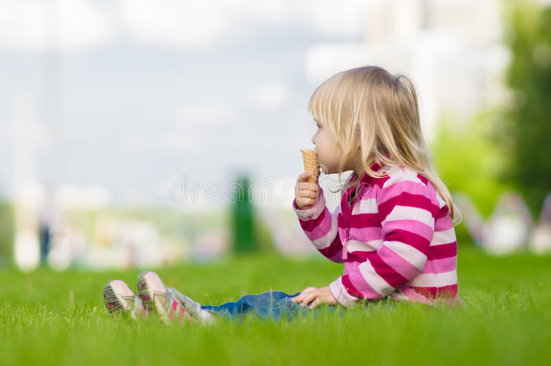 La muchacha adorable come el helado en hierba imagen de archivo libre de regalías