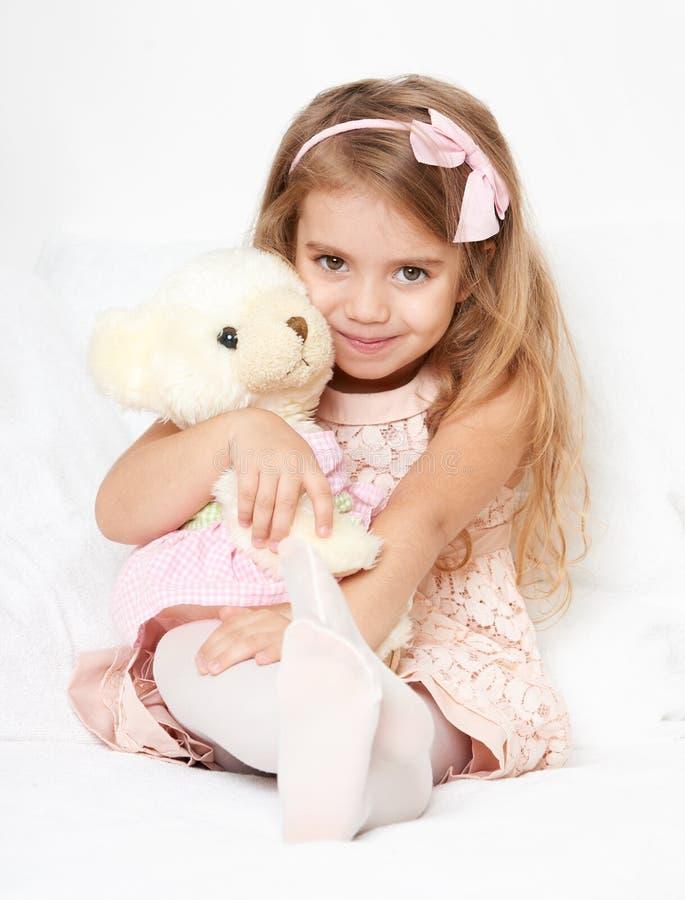 La muchacha adorable del pequeño niño se sienta en la cama con su juguete La muchacha del niño abraza el oso de peluche imagenes de archivo