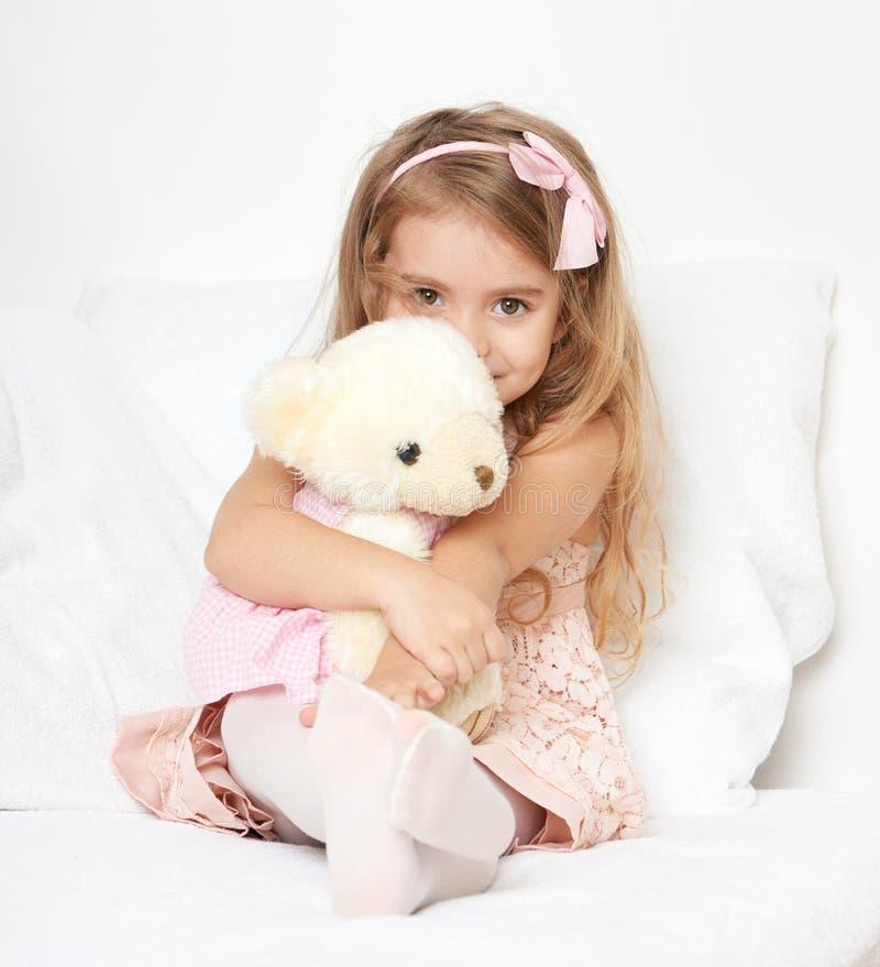 La muchacha adorable del pequeño niño se sienta en la cama con su juguete La muchacha del niño abraza el oso de peluche fotos de archivo