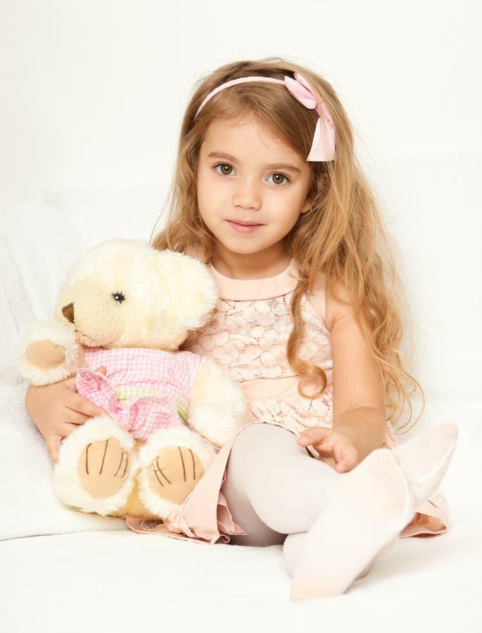 La muchacha adorable del pequeño niño se sienta en la cama con su juguete La muchacha del niño abraza el oso de peluche imágenes de archivo libres de regalías