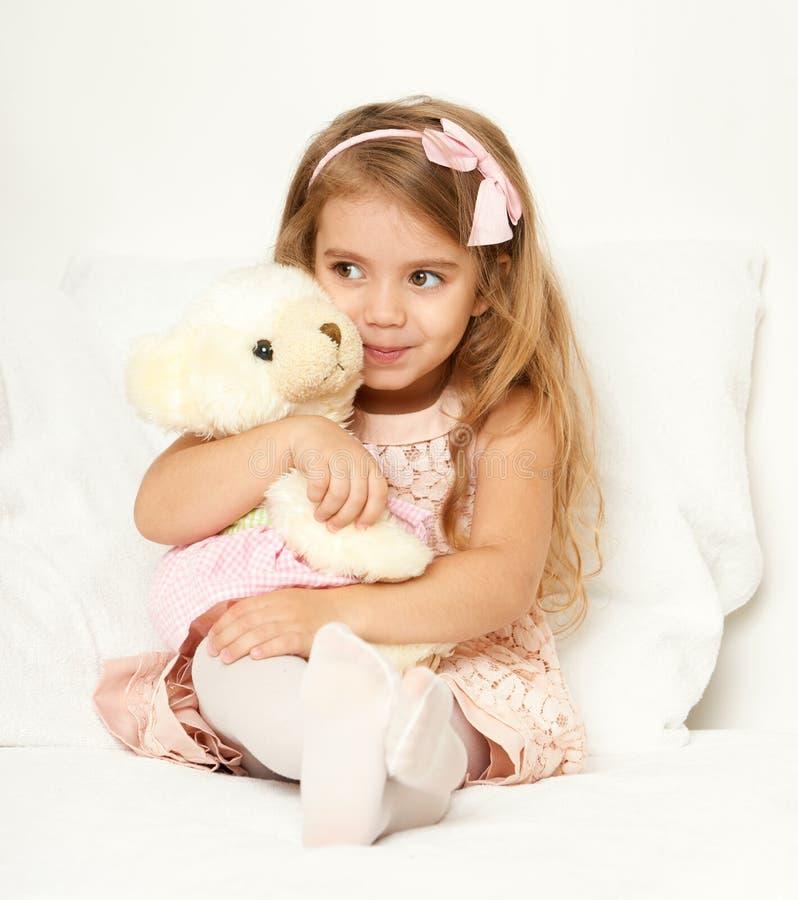 La muchacha adorable del pequeño niño se sienta en la cama con su juguete La muchacha del niño abraza el oso de peluche foto de archivo libre de regalías