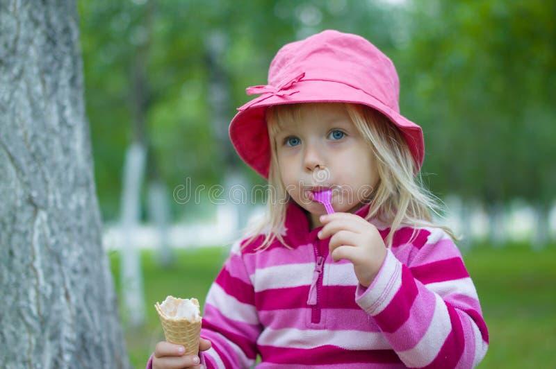 La muchacha adorable en sombrero rojo come el helado bajo árboles imágenes de archivo libres de regalías
