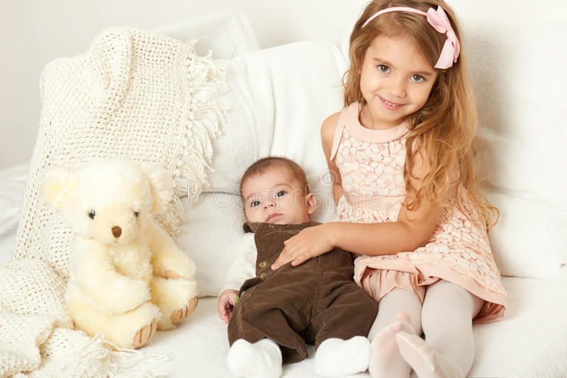 La muchacha adorable y el muchacho del pequeño niño se sientan en la cama con el oso de peluche fotografía de archivo libre de regalías