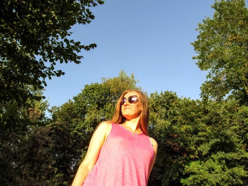 La muchacha adulta con el pelo rubio largo en gafas de sol mira en la distancia, sonriendo Retrato de una mujer joven contra el c imágenes de archivo libres de regalías