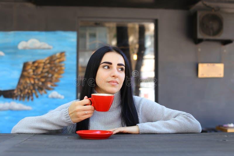La muchacha adulta joven linda sonríe, sostiene la taza disponible, mira la cámara imagenes de archivo