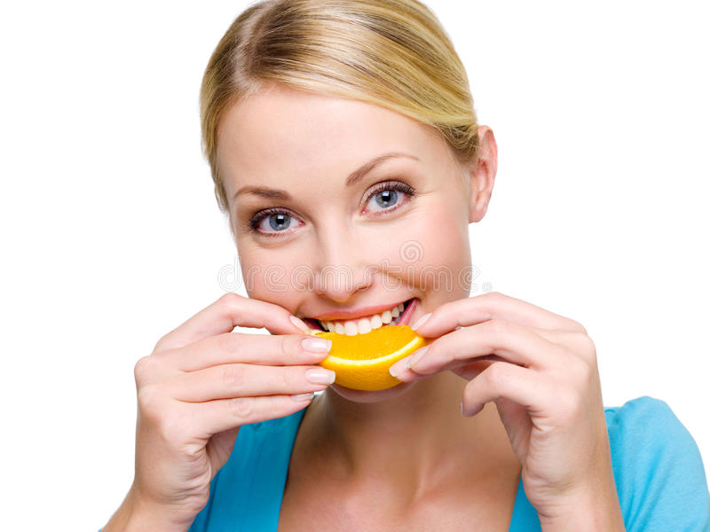 La muchacha adulta sonriente come la naranja fresca imagen de archivo libre de regalías