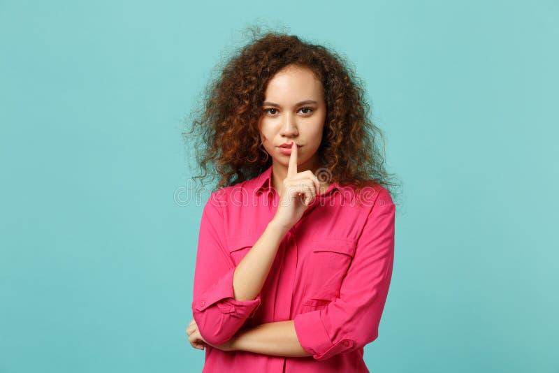 La muchacha africana atractiva en ropa casual que dice silencio sea reservada con el finger en gesto de los labios shhh aislado e foto de archivo