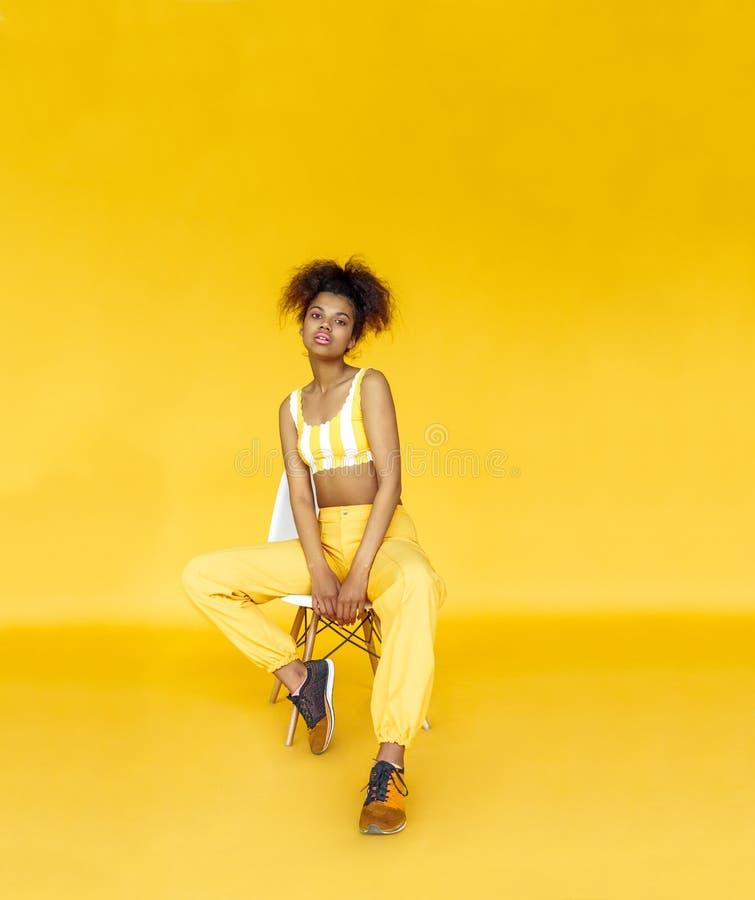 La muchacha africana de la moda que mira la cámara se sienta en la silla aislada en la pared amarilla imagenes de archivo