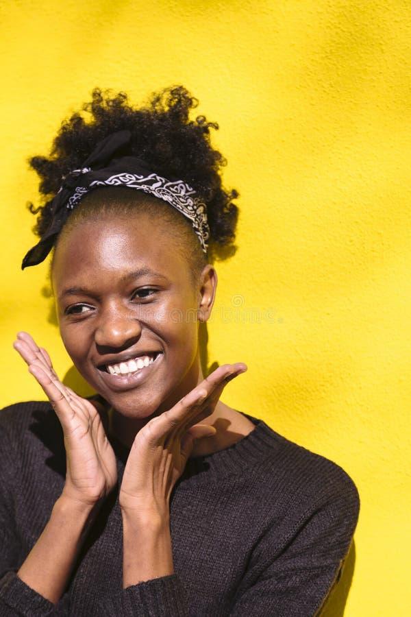 La muchacha africana feliz joven trajo las manos a su cara fotos de archivo