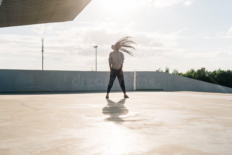 La muchacha africana positiva activa hermosa en ropa de deportes está sacudiendo su cabeza en sunlits imagenes de archivo
