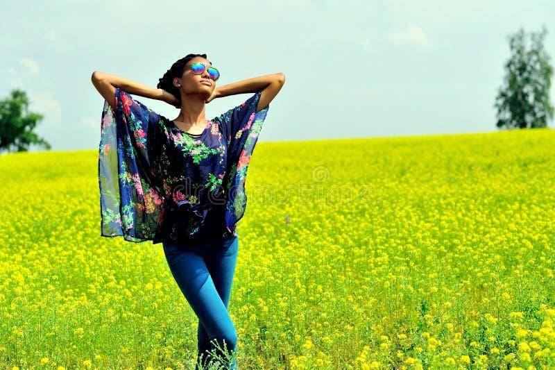 La muchacha afroamericana se coloca en el campo con las flores amarillas y mira el sol fotografía de archivo libre de regalías