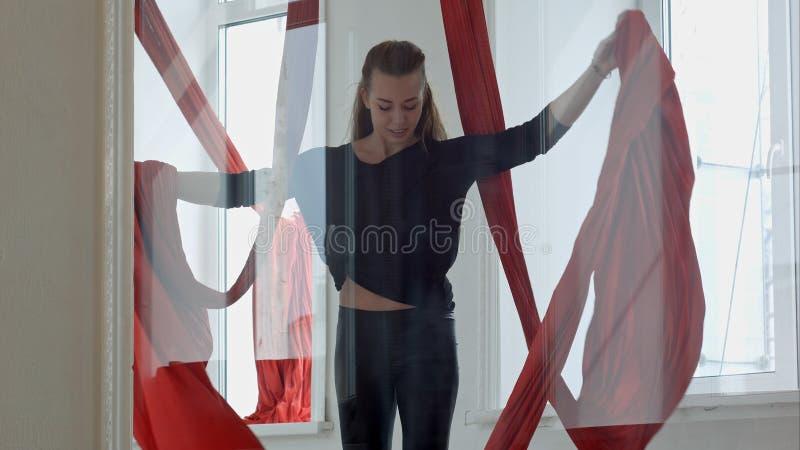 La muchacha agradable que hace deportes ejercita con la seda aérea imagenes de archivo