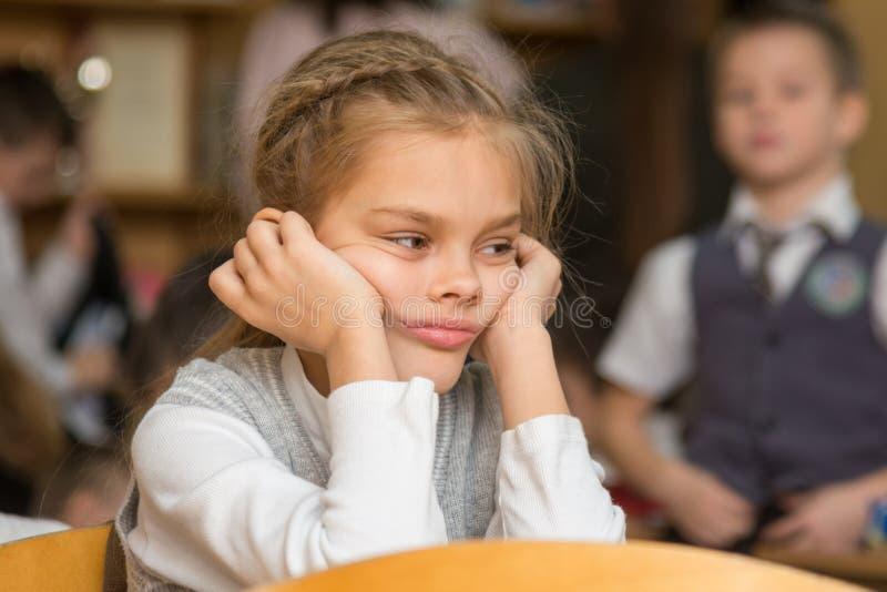 La muchacha agujereó en la escuela que se sentaba en un escritorio en revés fotos de archivo