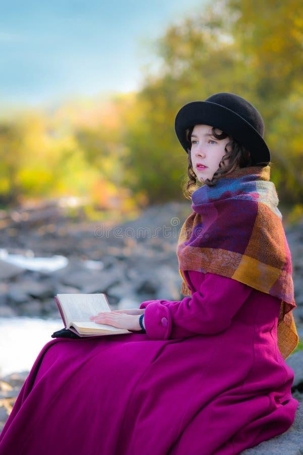 La muchacha al aire libre en capa brillante se está sentando y libro de lectura fotos de archivo
