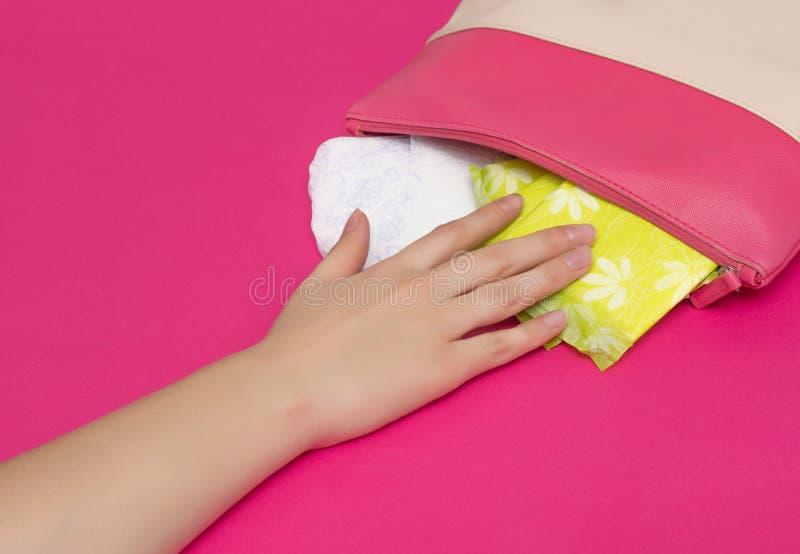 La muchacha alcanza hacia fuera a su monedero en el cual los cojines diarios de las mujeres por días críticos mientan, fondo rosa fotos de archivo