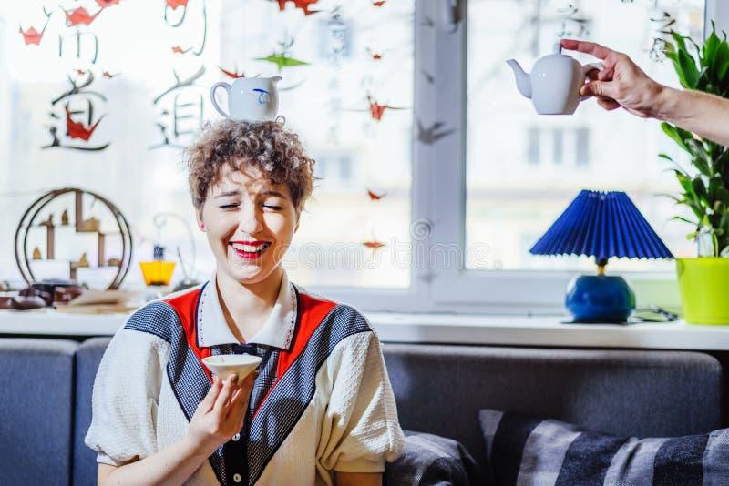 La muchacha alegre bebe té con una taza en su cabeza imagen de archivo libre de regalías