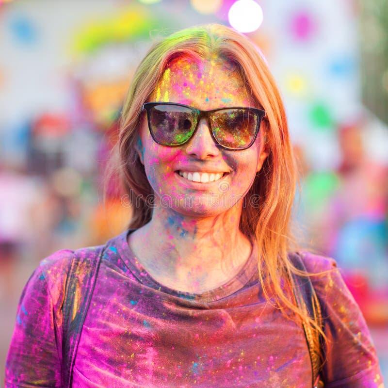 La muchacha alegre celebra el festival del holi de las pinturas foto de archivo