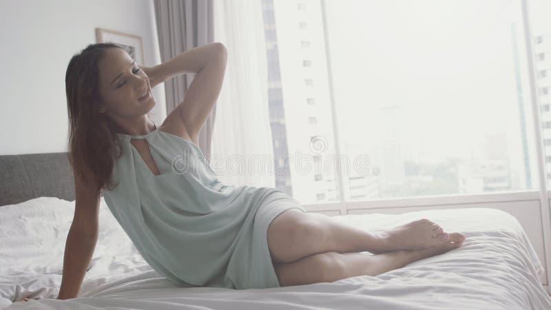 La muchacha alegre de la morenita sensual joven se sienta en la cama con los ojos cerrados, tentación, cuerpo femenino hermoso, l fotos de archivo libres de regalías