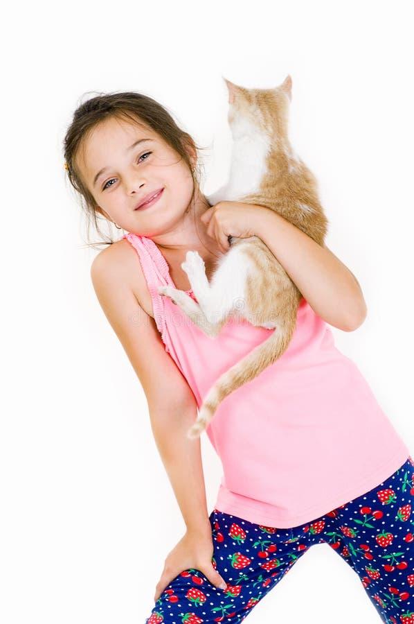 La muchacha alegre del niño juega con un pequeño gatito en un fondo ligero fotos de archivo