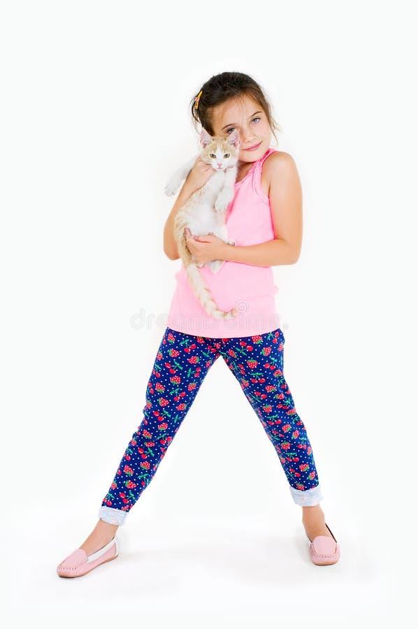 La muchacha alegre del niño juega con un pequeño gatito en un fondo ligero fotografía de archivo
