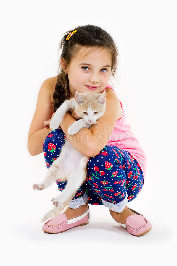 La muchacha alegre del niño juega con un pequeño gatito en un fondo ligero imagenes de archivo