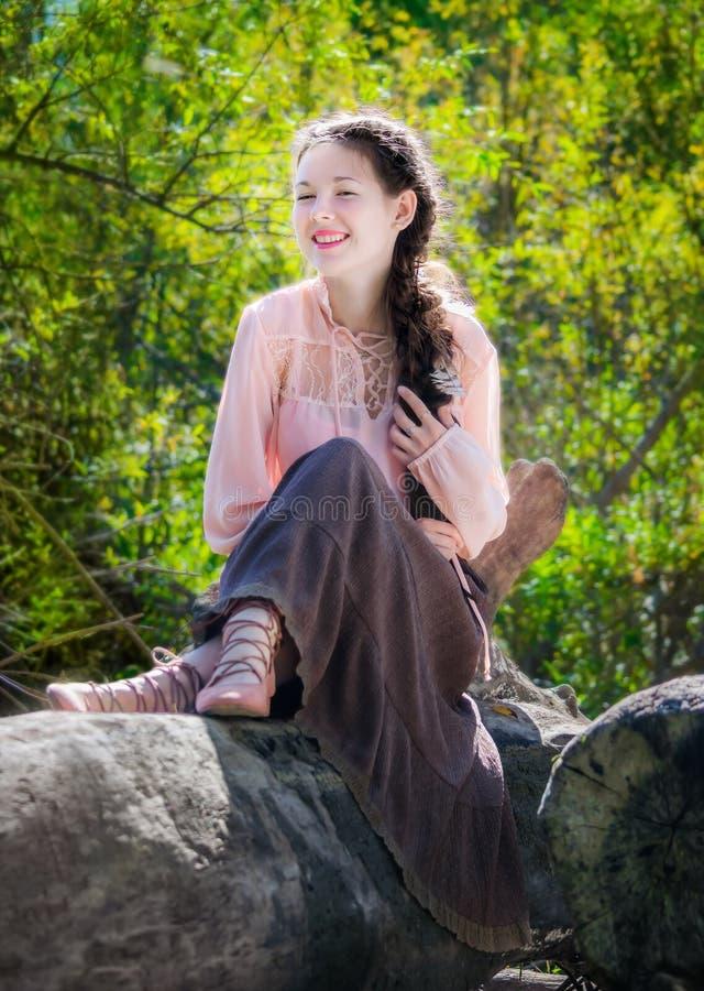 La muchacha alegre en el estilo de un boho se sienta en bosque foto de archivo libre de regalías